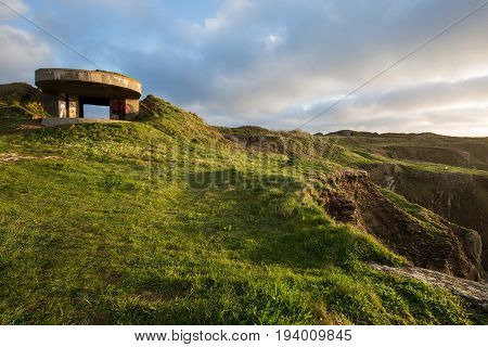 Bunker built on French cliffs during the second world war overlooking grassland coast and Atlantic ocean on a bright sunny day