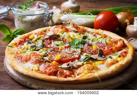 Fresh homemade pizza with vegetables and herbs