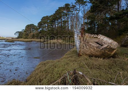 Forgotten remains of a grounded wooden boat on the shore at the estuary and sea lagoon. La Ria Le Conquet France