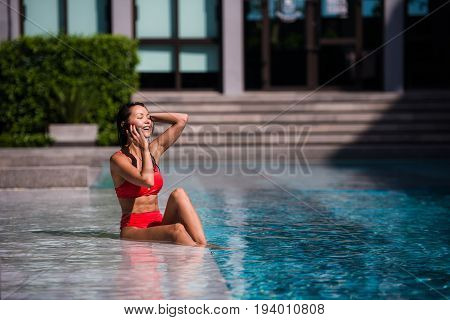 Attractive woman talking on her mobile phone by the poolside.