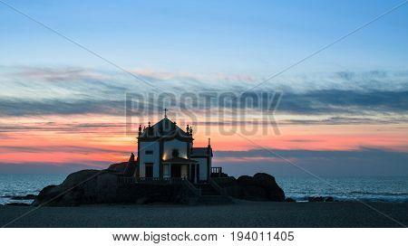 Chapel Senhor da Pedra at Miramar Beach at night time, Atlantic ocean, Porto, Portugal.