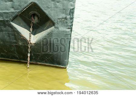 Prow of old rusty dark ship with anchor chain anchored in green Danube river. Novi Sad, Serbia.