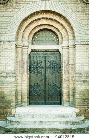 Big double wooden door at Synagogue with arch, stairs and brick wall in Novi Sad, Serbia.