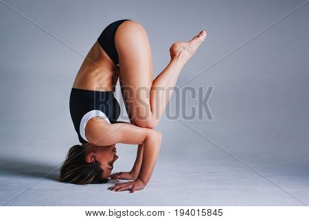 Young sports brunette woman standing upside down in yoga pose on gray background