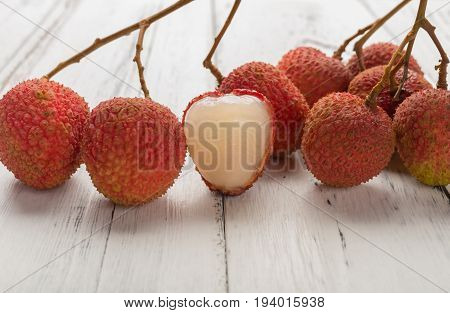 fresh lichees with one piece half peeled on white wood background