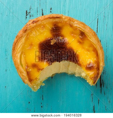 top view studio shoot of portuguese egg tart with a bite on a wood background