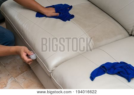 cleaning leather sofa with sponge and towel at home