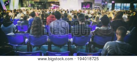 A lot of young people in a big hall listening to a speaker