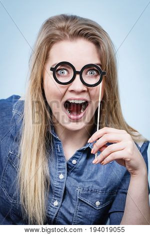 Happy shocked woman holding fake eyeglasses on stick having fun. Photo and carnival funny accessories concept.