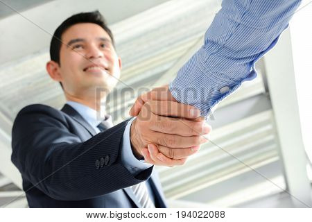 Businessmen making handshake with smiling face - greeting dealing merger and acquisition concepts