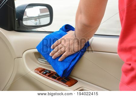 Hand cleaning interior car door panel with microfiber cloth