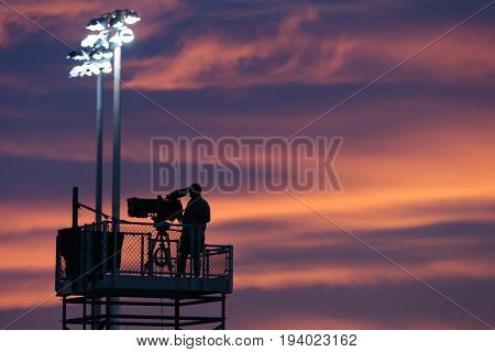 Silhouette of a tv cameraman at sunset