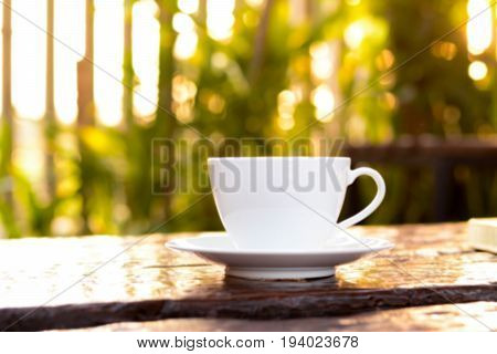 Blurred coffee cup on old wood table in natural green background