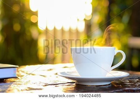 Hot coffee in the cup on old wood table with blur natural green background - soft focus