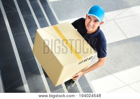 Deliveryman walking up stairs carrying a big parcel box