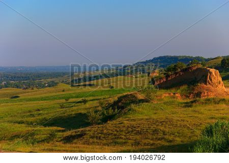 The cross-country terrain with hills and sites of trees and the woods is lit with low morning light. Below small settlement farm. Krasnodar Krai Kuban Russia.
