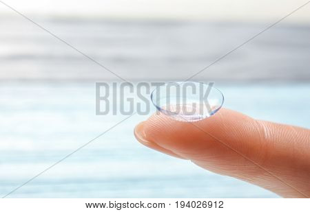 Female finger with contact lens on blurred background