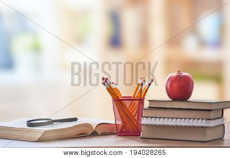 Back to school and happy time! Apple, pile of books and pencils on the desk at the elementary school.