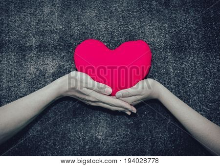 Young man giving a heart-shaped pillow his sweetheart on Valentine's Day. Love beautiful concept isolated on white background.