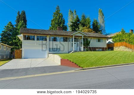 Expanded family house with wide garage concrete driveway and mowed lawn on the front yard