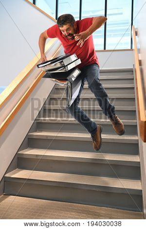 Hispanic businessman falling on stairs while carrying binders