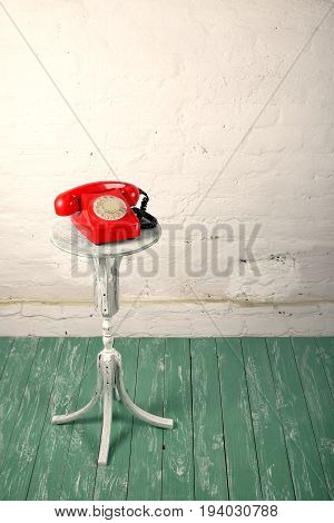 Retro style - Red vintage phone old flowers plant stand on a wooden green and a white brickwork background.