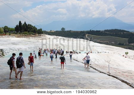 Pamukkale, Turkey - May 28 2017: A lot of people at the entrance to the terrains of travertines. The most famous tourist attraction. Tourists against white calcium deposits. Hills. Blue sky background
