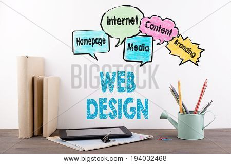 Web Design Concept.  Books and stationery on a wooden office desk.
