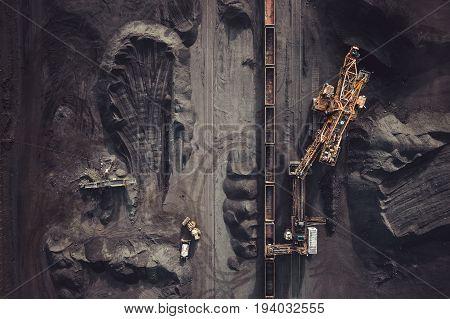 Coal mining. Aerial view. Excavator loading train cargos