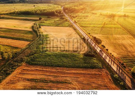 Beautiful aerial view of countryside and cultivated fields in sunset drone point of view