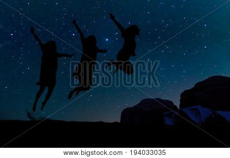 Silhouette of three people jumping on the sand hill beneath the stars Milky Way and a lot of stars over the mountain at Wadi Rum desert. Concept for happiness traveling and freedom.