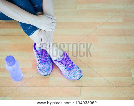 Woman leg wearing purple shoes with bottle of water on wooden floor background. exercise concept.