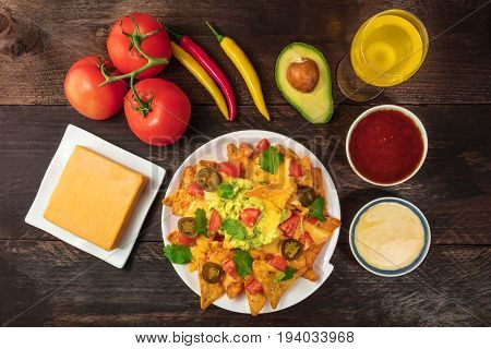 An overhead photo of nachos with queso, traditional Mexican snack, with ingredients like tomatoes, chilli peppers, Cheddar cheese, avocado, and white and red sauces, with a place for text