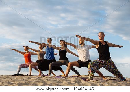 Mixed race group of people exercising yoga healthy lifestyle fitness warrior poses. Concentration.