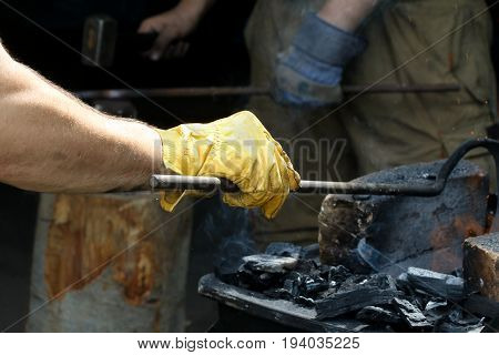Two blacksmiths working with anvil hammer and iron