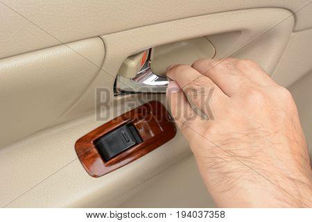 Hand pulling car interior door handle opening car door