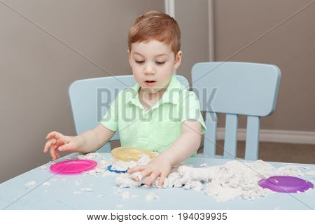 Portrait of funny cute white Caucasian boy playing kinetic sand indoors at kindergarden. Early creativity brain development concept. Children home activity. Fine motor skills.