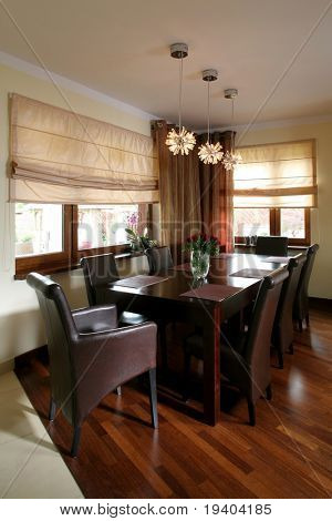 A beautiful dining room with wooden table and chairs, in a luxurious house