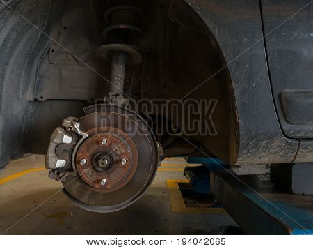 Front disc brake on car in a garage. Auto mechanic repairing .