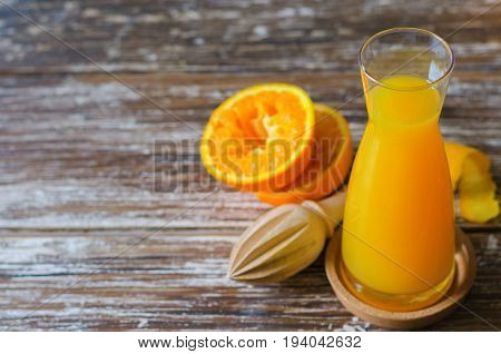 Freshly squeezed orange juice organic squeezed oranges fruit and wooden citrus juicer on dark wooden table.Space for text.