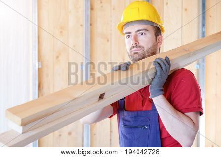 Carpenter worker holding wooden boards in a building site