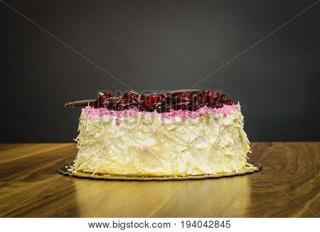 Delicious Creamy Whole White Chocolate Cake With Cherries On Top On Dark Background