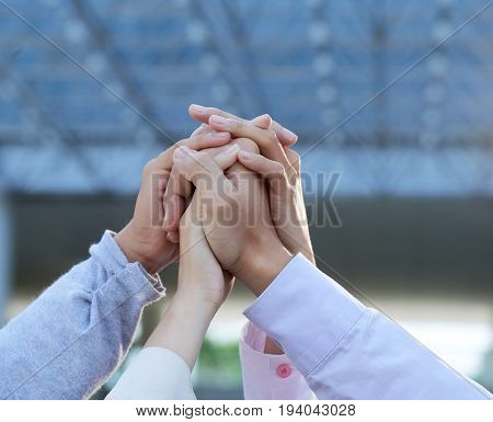 Clasped hands of business people raised to express togetherness