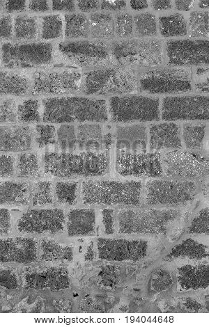 rough porous texture of stone bricks of an old and ancient wall of monochrome tone