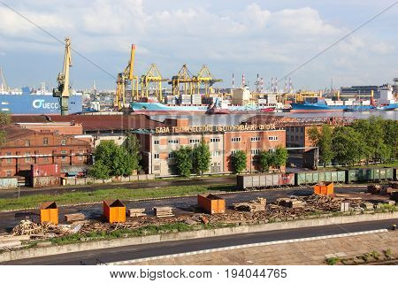 St. Petersburg, Russia - June 25 2017: The cargo port building. Containers with goods are loaded / unloaded on a commercial vessel using a crane in the harbor of the city. Business transport concept