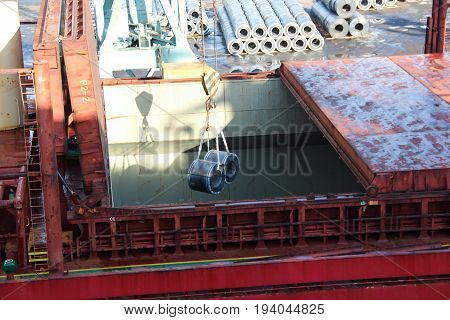 Loading huge aluminium coils as raw materials for heavy industry, instrumentation and engineering to the hold on the trading ship with a built-in ship's crane in the warehouse of the port city