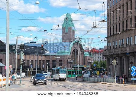 Helsinki, Finland - 28 Jun 2017: Day view of the city: the main railroad station with the clock tower and street with shopping complex with the tram and cars on the background of blue summer sky