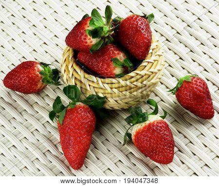 Arrangement of Big Ripe Strawberries in Wicker Bowl closeup on White Wicker background