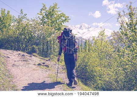 Traveler With Big Backpack Is Climbing Heavily Along A Mountain Road