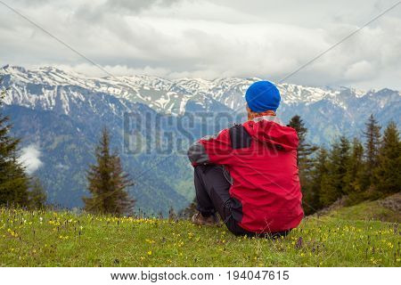 Dreaming Traveler Sits On The Alpine Meadow